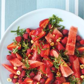 Салат из арбуза, малины, клубники и мяты на тарелке